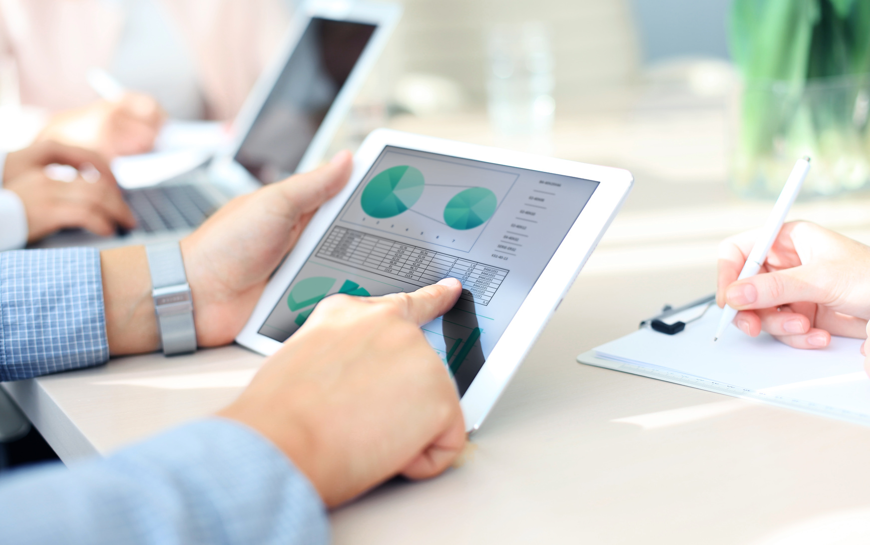 business_person_analyzing_financial_statistics_displayed_on_the_tablet_screen