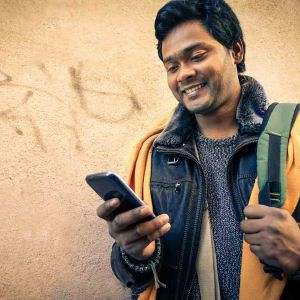Young indian man holding mobile phone