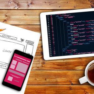 website wireframe sketch and programming code on digital tablet